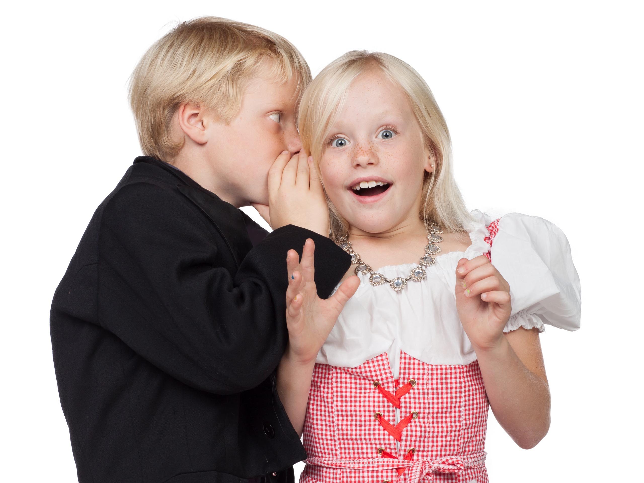 Young boy whispering in the ear of a girl that looks excited.