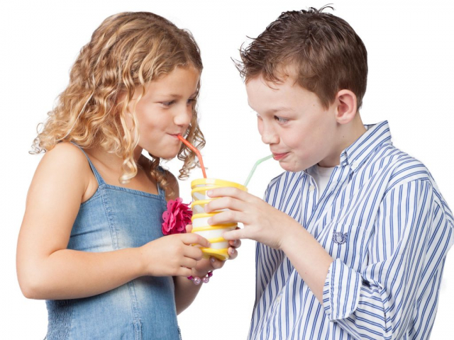 Boy and girl drinking with a straw from the same glass.