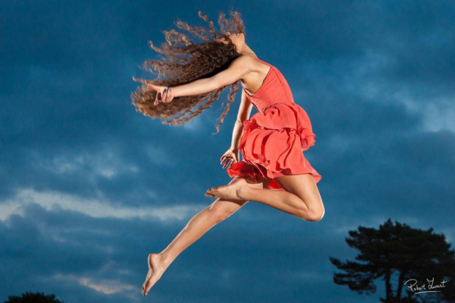 Actionphoto of a young female dancer in front of dark clouds with highspeed flashes.