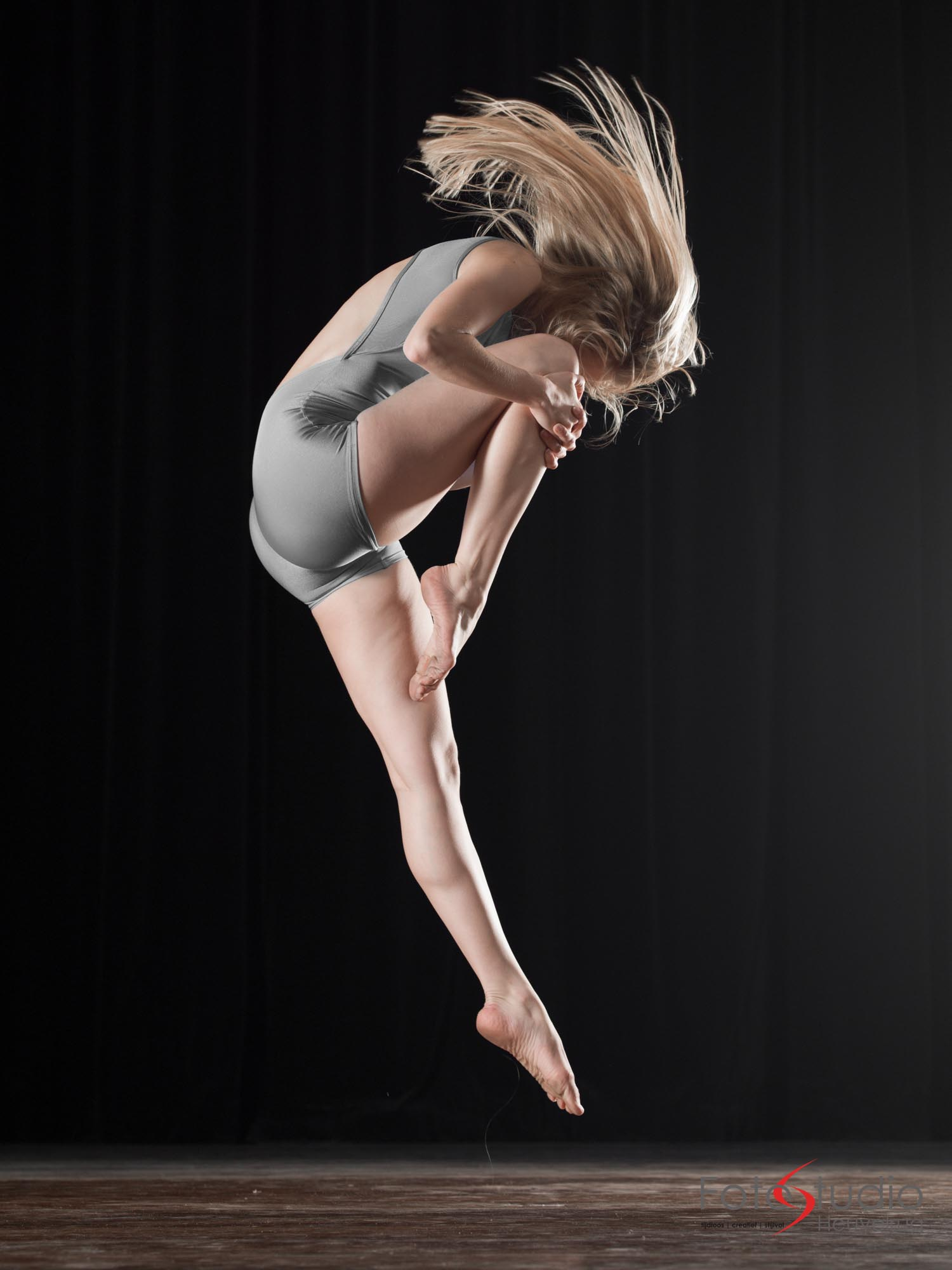 Young female dancer jumps while her hair is moving.