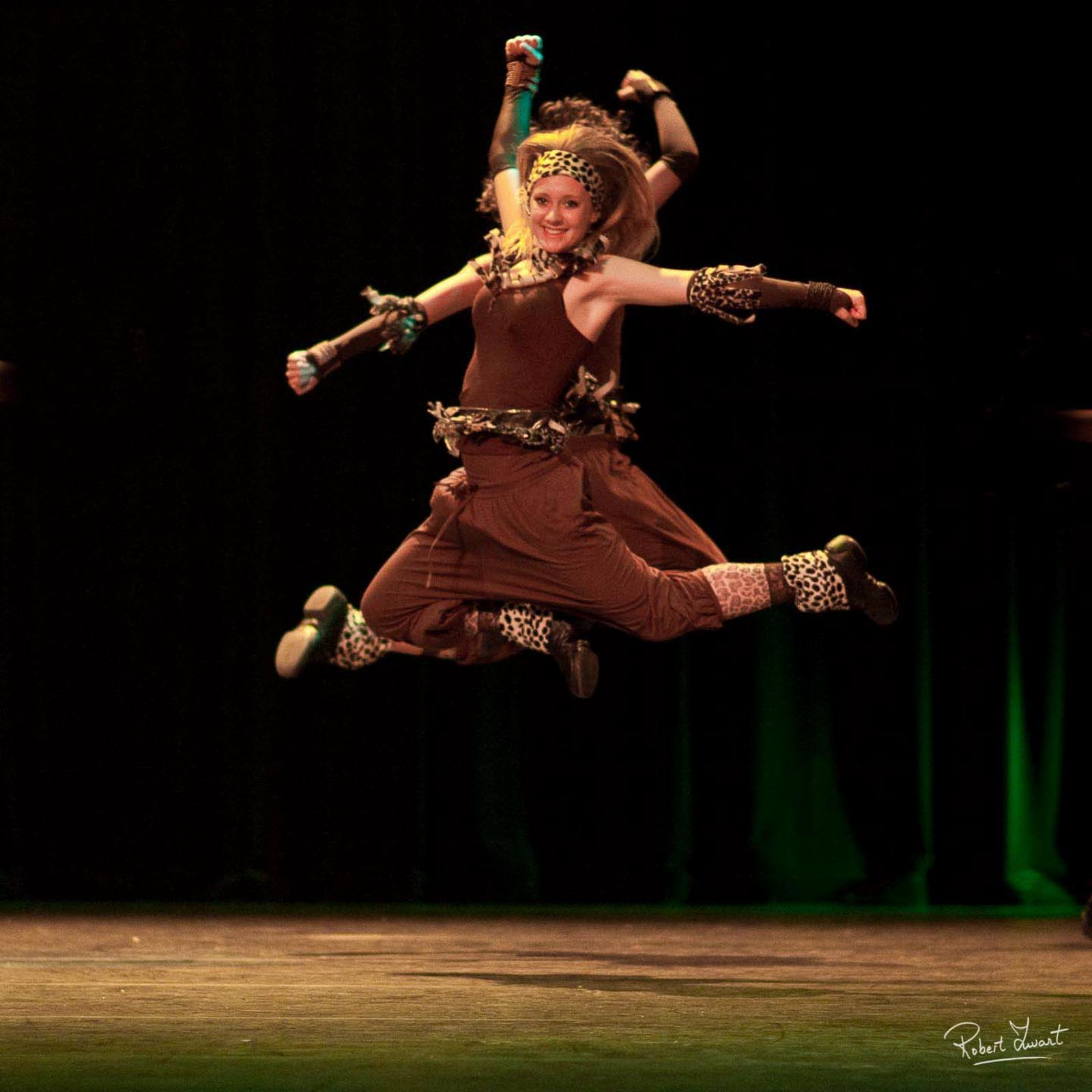 Two female dancers on stage shot during their jump.