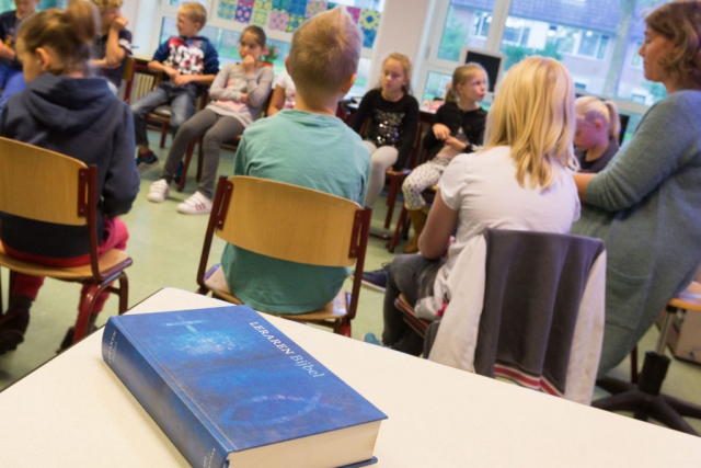 Class with children, sitting in a circle, with a bible on the foreground