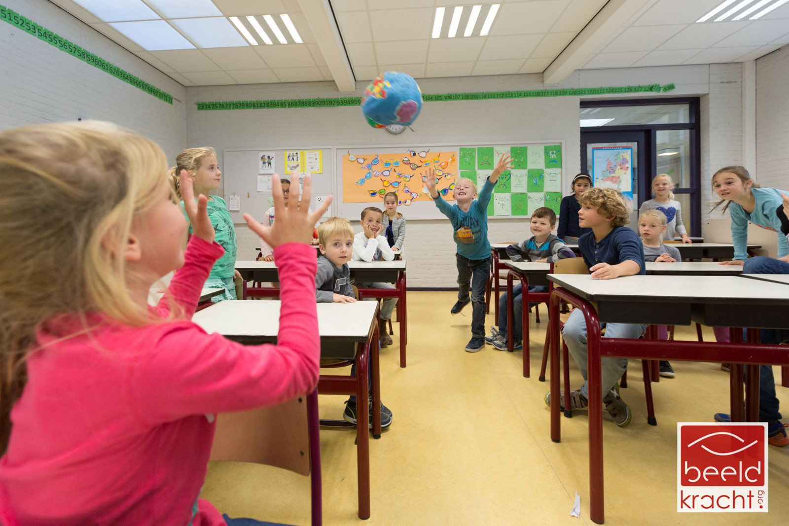 Children in a classroom throwing a worldball to each other.