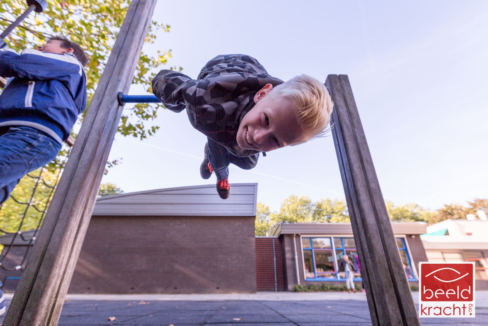 Boy having fun on a climbing frame on the playground of the school.