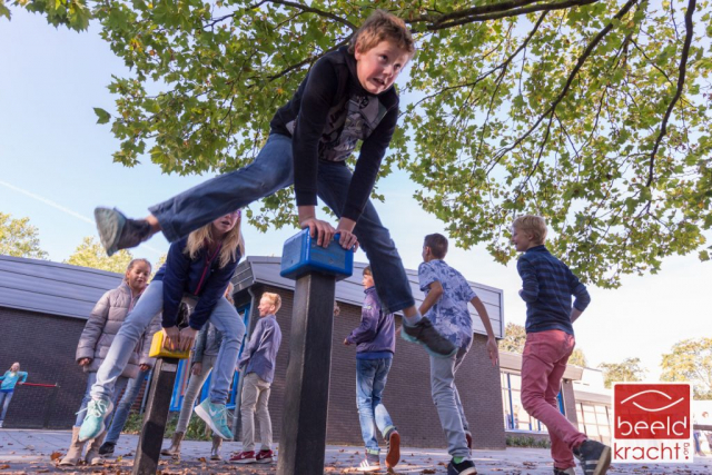 Young boys and girls playing on the playground of the school.