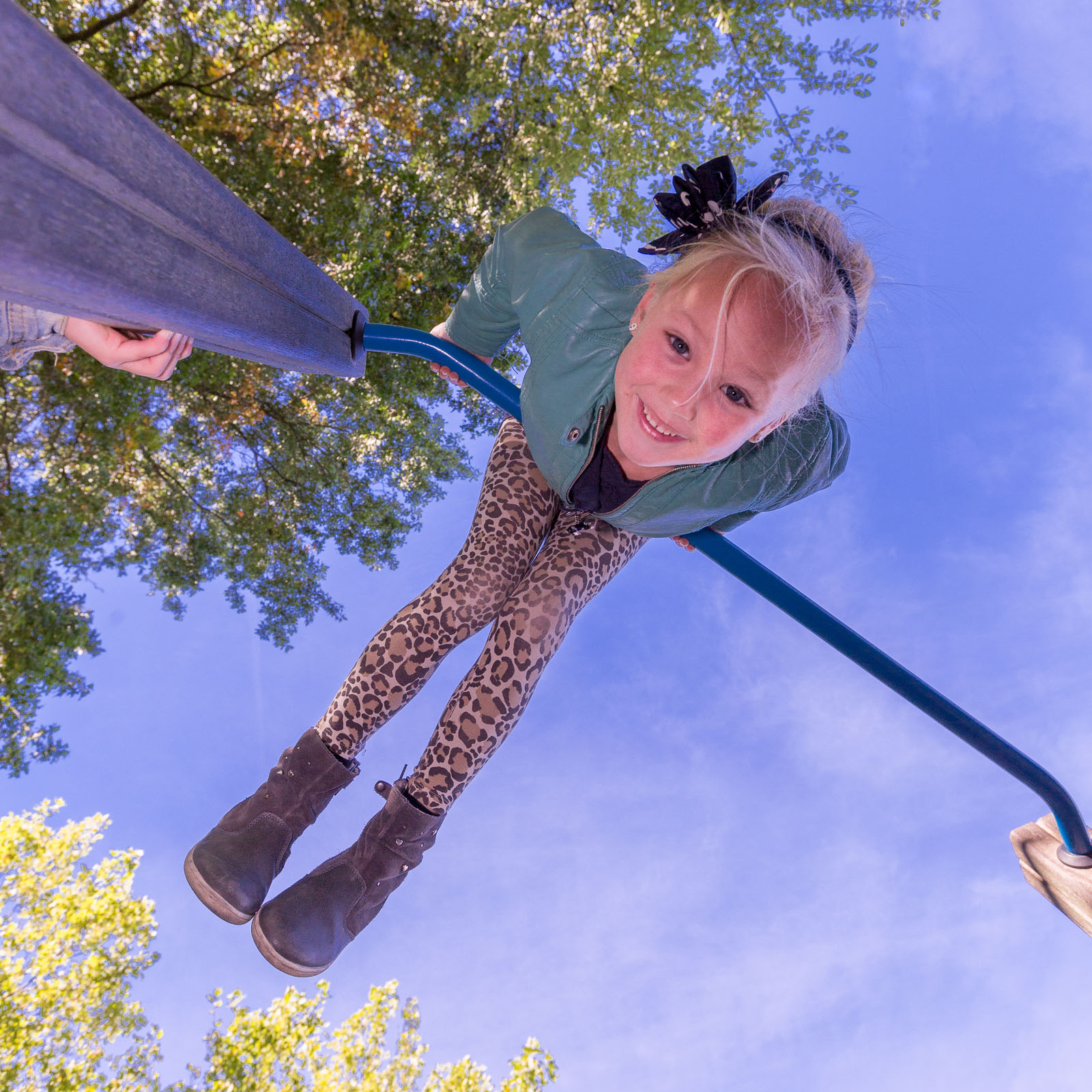 Young girl playing in a playground on a horizontal bar with frog perspective