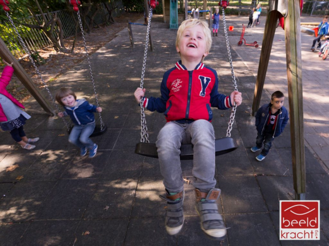 young boy playing on a swing set.