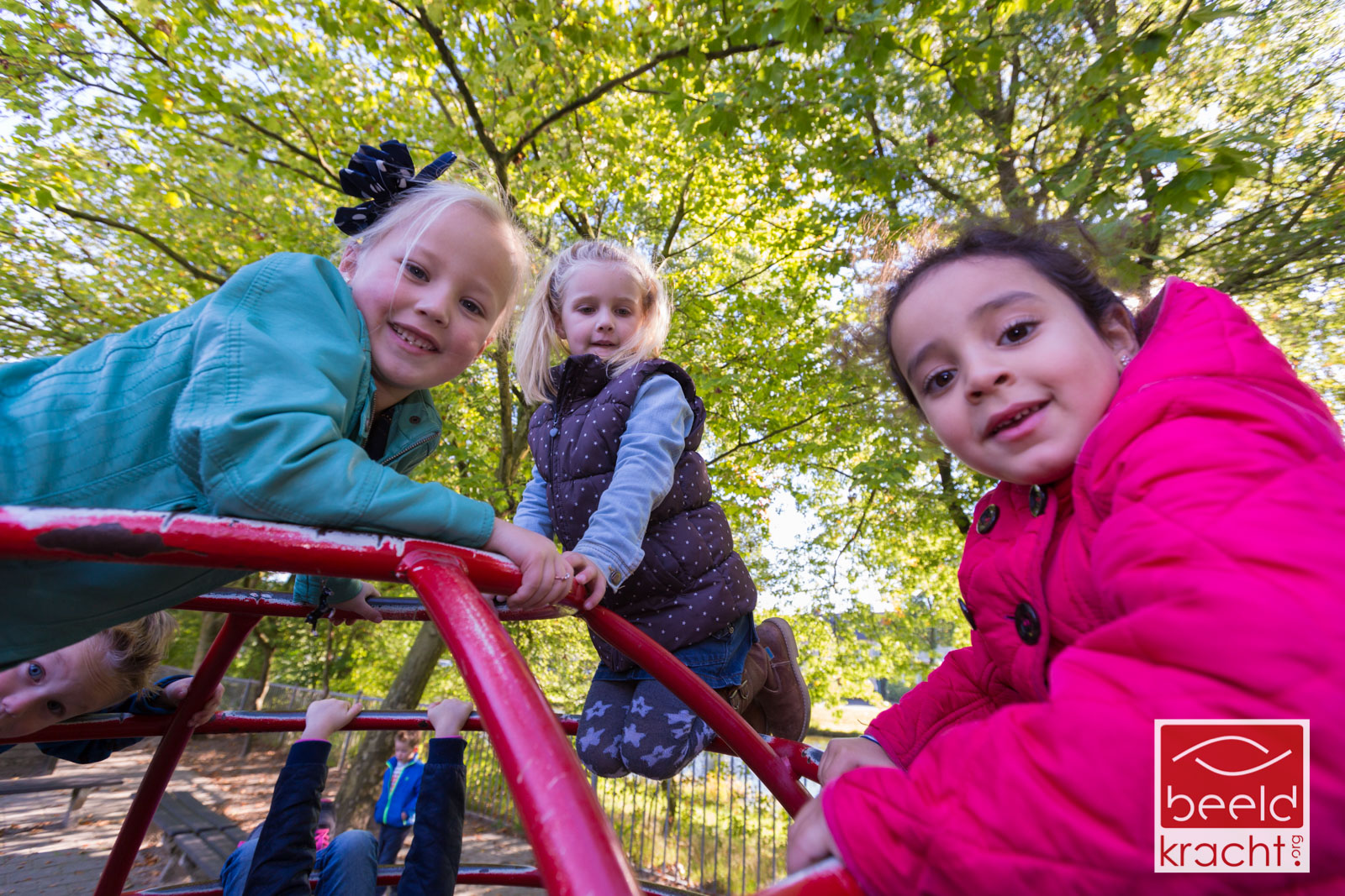 Three young girls photographed on a climbing frame in the playground of the school.