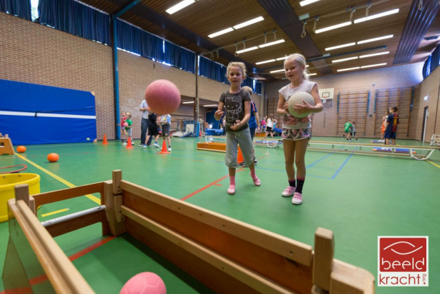 Two young children aiming their ball in a sportshall of a school.